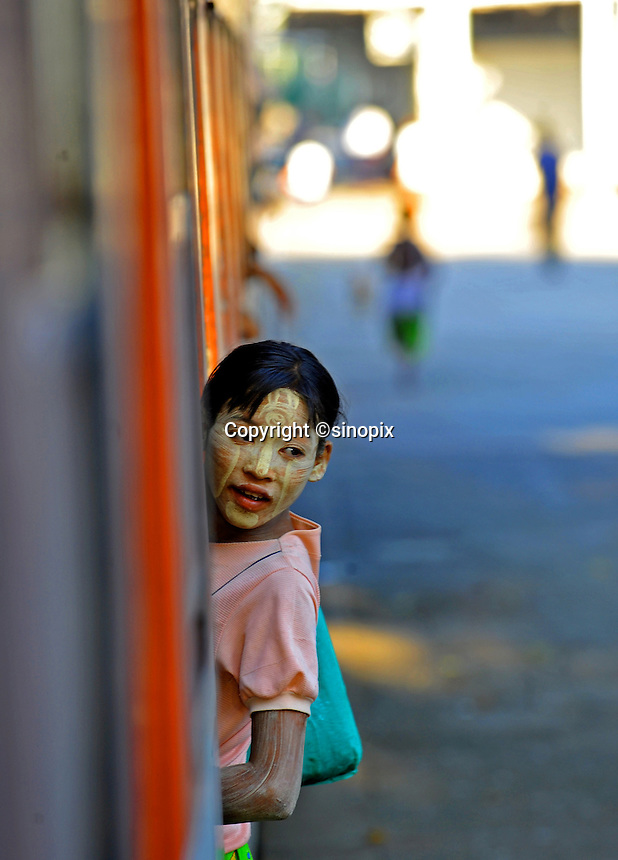 A young vendor with her face painted with rice paste to protect from the sun on the Mandalay to Rangoon train , Burma Nov 2008.  <br /> <br /> Photo by Richard Jones