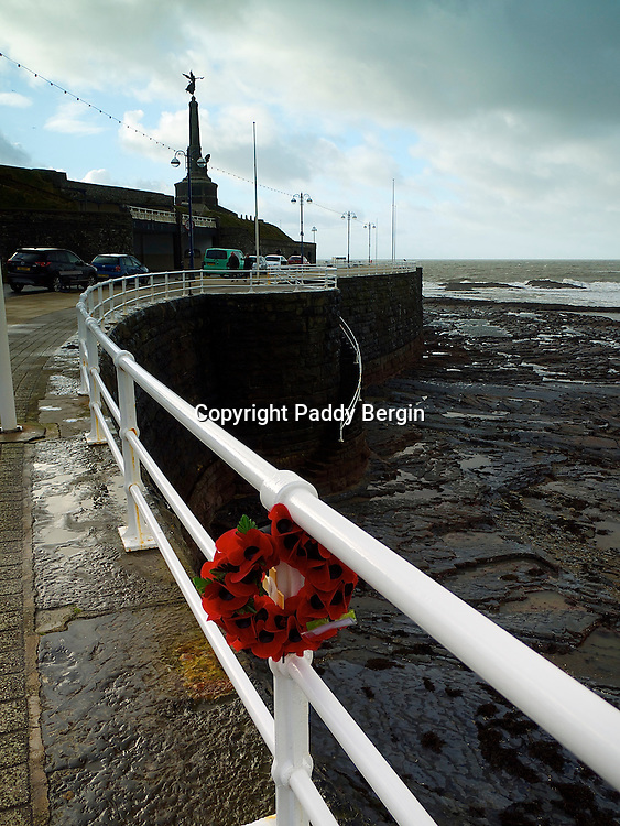 A poppy wreath attached to the railings on Aberystwyth Promenade.<br /> <br /> Poppy fields of Flanders, during the 1st World War, poppies grew on the graves of soldiers and have become a symbol of remembrance for those who have died during wartime.<br /> <br /> Stock Photo by Paddy Bergin