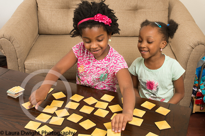 7 year old with her 6 year old sister playing memory game turning over cards on table