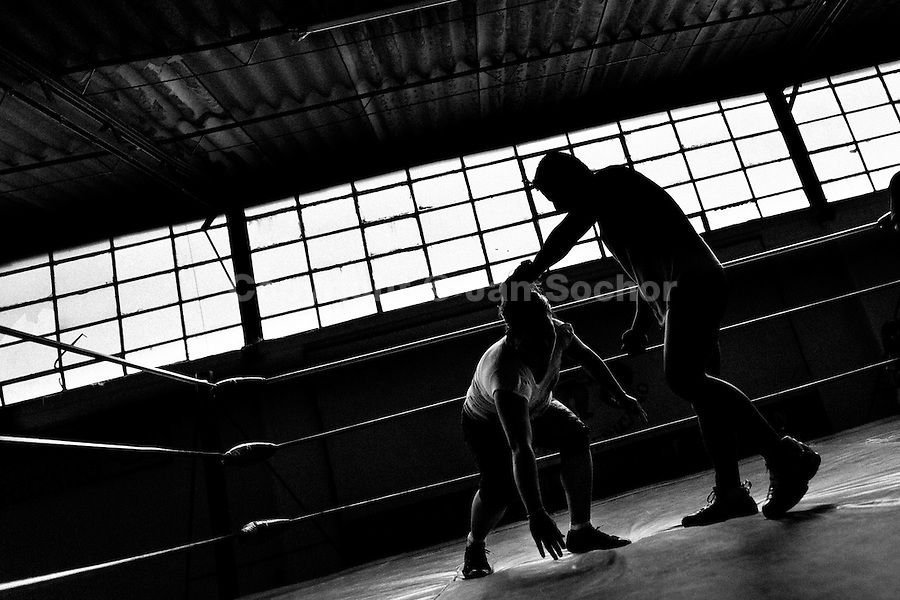 """A female Lucha libre wrestler trains with her male sparring partner at a combat sports gym in Mexico City, Mexico, 29 April 2011. Lucha libre, literally """"free fight"""" in Spanish, is a unique Mexican sporting event and cultural phenomenon. Based on aerial acrobatics, rapid holds and the use of mysterious masks, Lucha libre features the wrestlers as fictional characters (Good vs. Evil). Women wrestlers, known as luchadoras, often wear bright shiny leotards, black pantyhose or other provocative costumes. Given the popularity of Lucha libre in Mexico, many wrestlers have reached the cult status, showing up in movies or TV shows. However, almost all female fighters are amateur part-time wrestlers or housewives. Passing through the dirty remote areas in the peripheries, listening to the obscene screams from the mainly male audience, these no-name luchadoras fight straight on the street and charge about 10 US dollars for a show. Still, most of the young luchadoras train hard and wrestle virtually anywhere dreaming to escape from the poverty and to become a star worshipped by the modern Mexican society."""