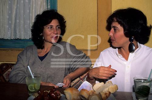 Sao Paulo, Brazil. Two smiling Brazilian women enjoying a caipirinha (sugar cane spirit with lime, sugar and ice).  Petiscos; bread and sausage.