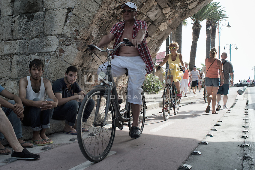 Tourists riding their bicycles past a group a Syrian migrants. Kos, Greece. Sept. 7, 2015