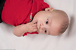 4 month old baby boy at home closeup on back sucking fingers