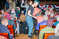 """Warren campaign National Event Organizer Jace Ritchey hands out campaign signs to attendees before Democratic presidential candidate and Massachusetts senator Elizabeth Warren speaks at Rochester Opera House in Rochester, New Hampshire, on Mon., Feb. 10, 2020. This is the final day of campaigning before voting in the primary happens on Feb. 11. Warren has fallen to 4th or 5th place in recent polls. Ritchey's earrings read """"They"""" and """"Them,"""" which are their preferred pronouns."""