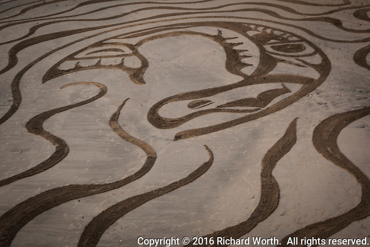 At the center of a massive sand-art creation on a California beach, a whale.