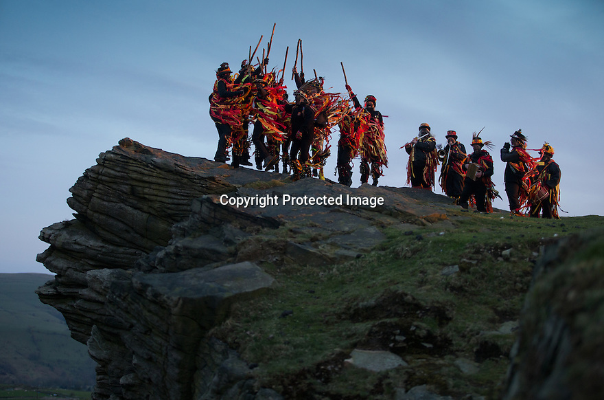 01/05/16<br /> <br /> At the break of dawn, with the weather forecast promising a much warmer week ahead, the sun rises on a group of Border Morris Dancers celebrating May Day with a traditional performance, Dance up the Dawn, on top of Windgather Rocks, a gritstone crag near Whaley Bridge on the Derbyshire - Cheshire Peak District border.<br /> <br /> The Powderkegs, a group of 16 dancers, paint their faces black, wear rag jackets and jingle bells on their legs.<br /> <br /> The group formed in 2001, and took their name from local gunpowder mills.<br /> <br /> Their traditional style of dance is noisy, colourful and explosive.<br /> <br /> The dancers and musicians, both men and women, wear red, yellow, gold and orange rag jackets and trousers to signify fire and explosions. <br /> <br /> A selection of sparkly materials adds to the  flame effect when they dance.<br /> <br /> It is believed that the Border Morris Dancers' costume dates back to the time of tied workers, in the early 19th century, when extra money could be made at fairs dancing and playing music. <br /> <br /> The workers would be evicted if caught by the squire so they used materials close to hand - rags and coal dust to disguise themselves. <br /> <br /> All Rights Reserved: F Stop Press Ltd. +44(0)1335 418365   www.fstoppress.com.