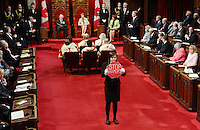 """Page Brigette DePape stands in the middle of the floor of the Senate as Governor General David Johnston delivers the Speech from the Throne in the Senate Chamber on Parliament Hill in Ottawa, Friday June 3, 2011. Moore has posted a giant photo on his website of 21-year-old Brigette DePape holding up a """"Stop Harper"""" sign in the Senate chamber during Friday's throne speech. THE CANADIAN PRESS/Sean Kilpatrick"""