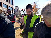 STAFF PHOTO BEN GOFF  @NWABenGoff -- 11/25/14 Alexander Ross holds a rose during a moment of silece for Michael Brown during a protest organized by the OMNI Center for Peace, Justice & Ecology in front of the Washington County Courthouse in Fayetteville on Tuesday Nov. 25, 2014. The demonstration was in response to the decision Monday night by the St. Louis County grand jury not to indict police officer Darren Wilson, who fatally shot Michael Brown in Ferguson, Mo.