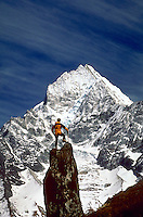 A climber on a rocky peak viewing snow covered Thamseku with blue sky in the background in the Mount Everest region of Nepal.<br />