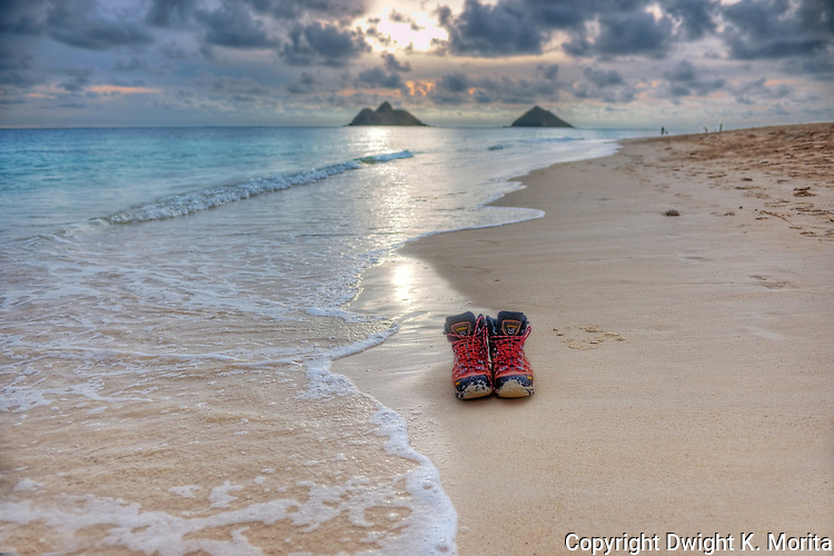 Hiking boots discarded at dawn on Lanikai Beach with the Mokulua Islands in the background.