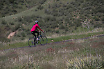 Woman cycling in Red Rocks State Park, Colorado .  John leads private photo tours in Boulder and throughout Colorado. Year-round.