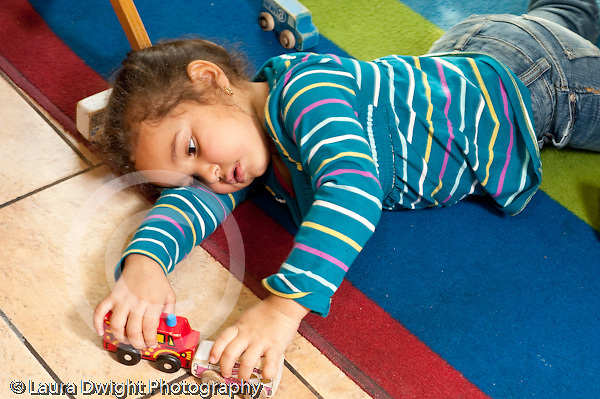 Education preschool 3-4 year olds imaginary play girl lying on floor playing by herself with two toy vehicles  horizontal alone