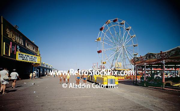 Wildwood Boardwalk & Aqua Circus in Wildwood, NJ. Tram Cars, Ferris Wheel & kids in bathing suits walking on the boardwalk.