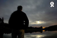 Man standing by water, dusk, rear view (blurred motion) (Licence this image exclusively with Getty: http://www.gettyimages.com/detail/200482367-001 )
