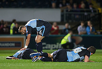 Paul Hayes of Wycombe Wanderers tends to Anthony Stewart of Wycombe Wanderers as he and Danny Rowe of Wycombe Wanderers go down after an attack in the air during the Capital One Cup match between Wycombe Wanderers and Fulham at Adams Park, High Wycombe, England on 11 August 2015. Photo by Andy Rowland.