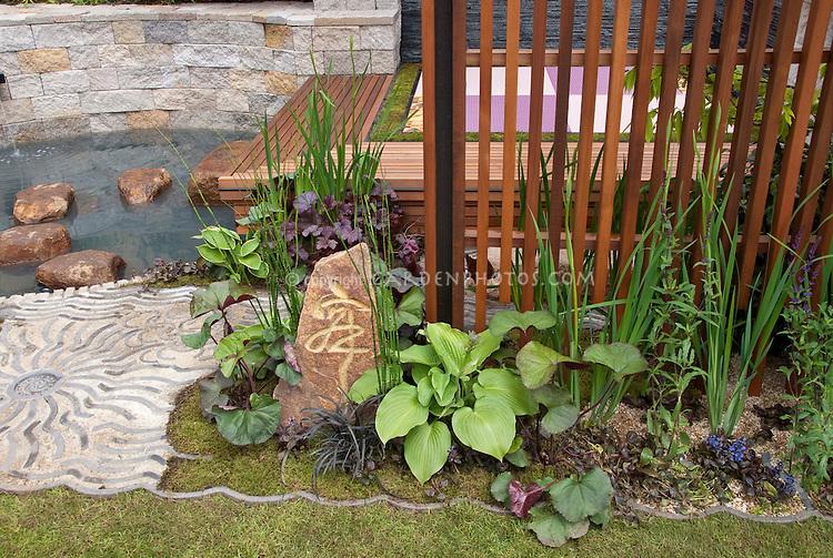 Japanese calligraphy ornament on garden stone, with Equisetum, Hosta, Heuchera in Asian theme Oriental garden, water feature, Ligularia, wooden deck, moss, patterns, curves, peaceful retreat