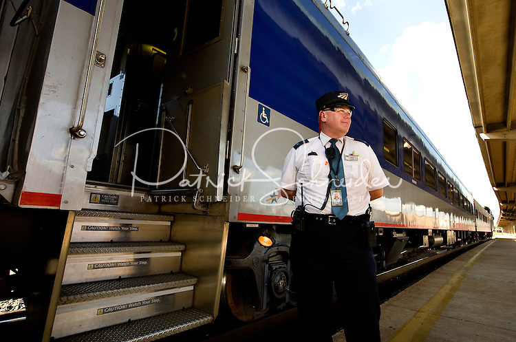 A conductor waits to help passengers board the North Carolina Amtrak in the Charlotte, NC, train station.