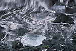 A chunk of ice rolls in the surf