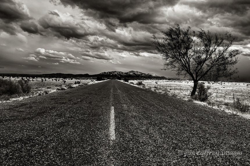 Black and white image of a long, straight, rough blacktop road leading to the Ortiz Mountains in the distance under a stormy sky.