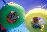 Kids peering through pool floats.