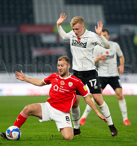 7th November 2020; Pride Park, Derby, East Midlands; English Football League Championship Football, Derby County versus Barnsley; Herbie Kane of Barnsley falls to his knees with the ball at his feet as he is tackled by Louie Sibley of Derby County