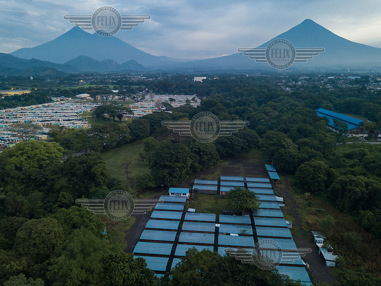Aerial view of a section of the Single-Family Transitional Shelters (ATUs in Spanish), the La Dignidad Housing Complex (on the left), and, from left to right, the Fuego, Acatenango and Agua volcanoes. Most families from La Trinidad have been living in the ATUs since late 2018, while families from other uninhabitable communities began receving their homes in the La Dignidad Housing Complex during 2019.