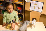 Day Care Center 2-3 year olds girl talking as she plays with toy animals