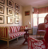 The living room is decorated in crisp red and white striped and checked fabric with a collection of black and white framed photographs on the wall
