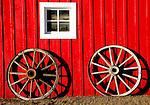 Wagon wheels against a red barn in Banff.