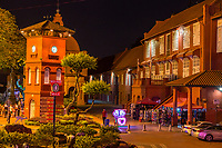 Stadthuys on right at night, Former Dutch Governor's Residence and Town Hall, Built 1650.  Illuminated Trishaw in center, waiting for tourists.  Melaka, Malaysia.