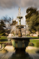 A water fountain captured in abstract, as in a dream - slow shutter and zoom. Water drops stretch up and out while the stoic fountain stands still.