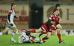 Scarlets wing Kristian Phillips finds support despite the efforts of Ulster centre Darren Cave to stop him..Celtic League.Scarlets v Ulster.Parc y Scarlets.02.12.12..©Steve Pope