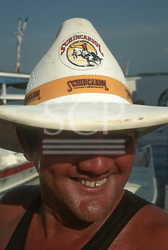 Amazonia, Brazil. Man with a diamond set in one of his front incisor teeth wearing a Schincariol beer leather hat.