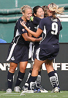 Lori Lindsey #6 and Allie Long #9 of the Washington Freedom congratulate Homare Sawa #10 after she scored Freedom's goal during a WPS match against St. Louis Athletica at RFK Stadium on July 18 2009, in Washington D.C. Freedom won the match 1-0.