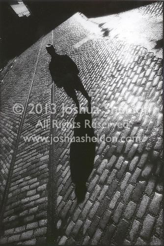 Man standing on cobblestone street