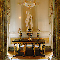 A Grecian statue stands in a niche above this console table which features ebony and gilt Egyptian figurines as legs