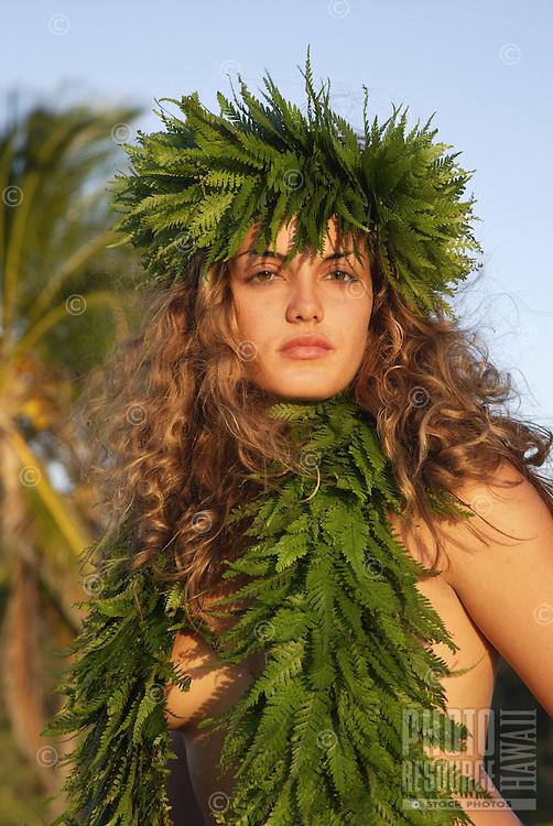Female (wahine) hula dancer wearing palapalai fern head lei, headshot.
