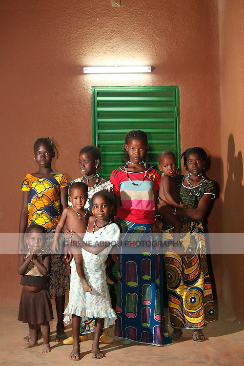 Young women and children line up for a nighttime photo in Djibo in northern Burkina Faso.