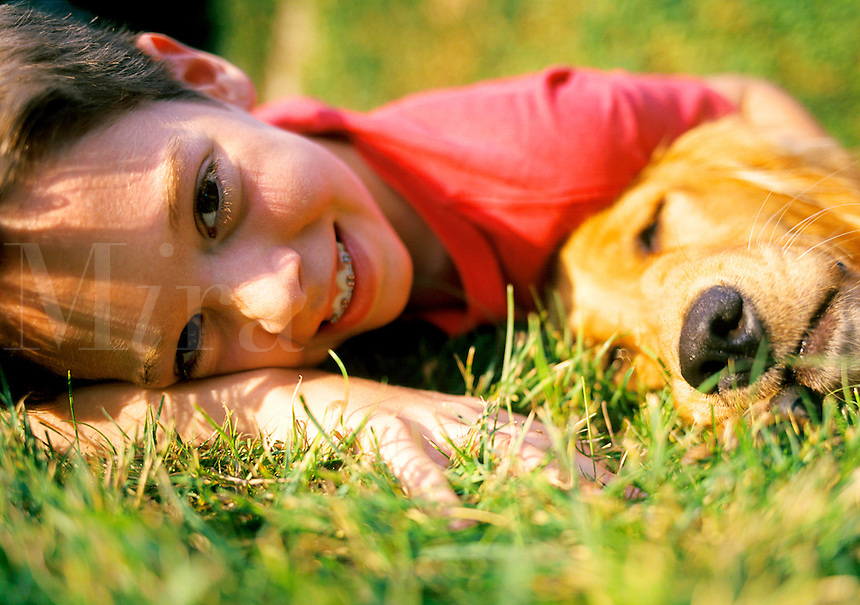 Teenage boy laying on lawn with his dog in summer