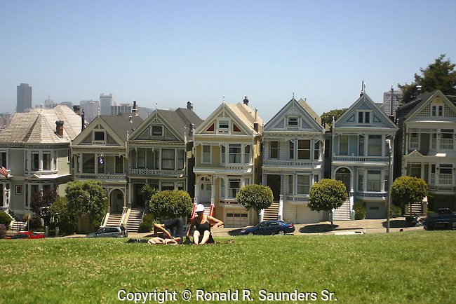 YOUNG WOMEN RELAX on GRASS in FRONT of VICTORIAN HOMES:(aka)PAINTED LADIES<br /> <br /> VICTORIAN HOMES in BACKGROUND
