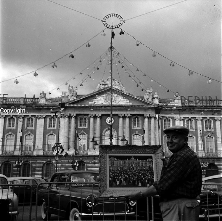 Le 12 Juillet 1961. Vue d'une personne posant avec un tableau sur la place du Capitole.