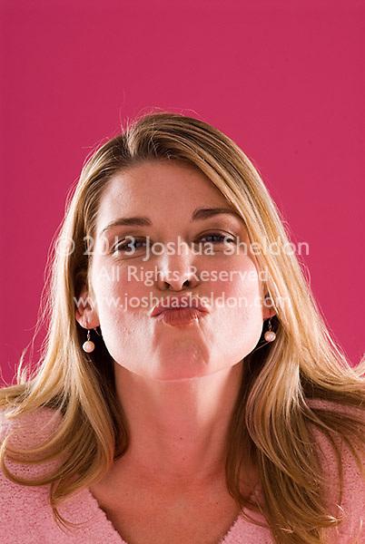 Studio portrait of young blonde Caucasian woman kissing