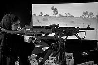 """United Arab Emirates (UAE). Abu Dhabi. Unmanned Systems Exhibition (UMEX 2020). Laser Shot - Firearms Training Simulators and Ranges, provides affordable, alternative training solutions for military. Laser Shot is a global leader and has remained committed to developing the most realistic and practical firearms simulators, crew training simulators, and live fire facilities available to the government and public. An Emirati woman with a black abaya shoots a M240 simulated recoil crew-served weapon on an interactive screen from the Laser Shot's Warrior Skills Trainer (WST). The """"Laser Shot Simulations"""" company enhances and increases readiness performance through individual, crew, section, platoon, and company maneuver battle drills and gunnery qualifications. The latest evolution in vehicular combat simulators, comprised of Mobile Marksmanship Training Simulators (MMTS), mockup HMMWV bodies and an arsenal of simulated recoil weapons. SMART™ training weapons transmit data back to Laser Shot's Weapons Interface software and accept compressed gas for the recoil system through a single umbilical into the weapon along with a data cable. The United Arab Emirates (UAE) is a country in Western Asia at the northeast end of the Arabian Peninsula. 24.02.2020  © 2020 Didier Ruef"""