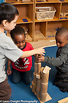 Education Preschool Headstart 3-4 year olds three boys building with wooden blocks together