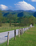 Great Smoky Mountains National Park, TN:  wooden fence line borders Hyatt lane in Cades Cove with clouds over the foothills of the Smoky Mountains in spring