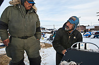 Volunteer checker helps Mike Williams fix a broken part of his sled at the Shageluk checkpoint during Iditarod 2009