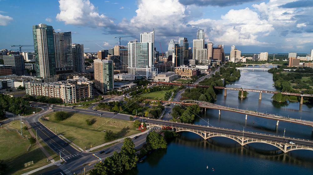 Beautiful aerial view of the downtown Austin Skyline overlooking Lady Bird Lake and the Lamar Boulevard Bridge, Lamar Pedestrian Bridge and Austin Graffiti Bridge on a gorgeous summer's day.
