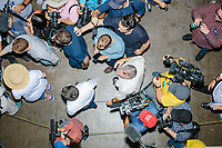 Media surround South Bend mayor and Democratic presidential candidate Pete Buttigieg as he walks through the agriculture building at the Iowa State Fair in Des Moines, Iowa, on Tues., Aug. 13, 2019.