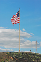 The American flag flying at the Veterans Memorial in Shelby, Montana. This flag flies 24/7. The Montana Big Sky making the perfect background of blue skies and billowy white clouds.