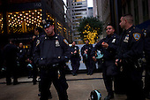 """New York, New York<br /> November 15, 2011<br /> <br /> Police rest on the east side of Broadway and Cedar Street after a long night of clearing Zuccotti Park of a protester's encampment. <br /> <br /> After the police clear Zuccotti Park many of the evicted """"Occupy Wall Street"""" protesters, reconvened in Foley Square.<br /> <br /> The protesters then marched to Juan Pablo Duarte Square at Canal and 6th Ave and final back to Zuccotti Park to wait a court order to reenter the park."""